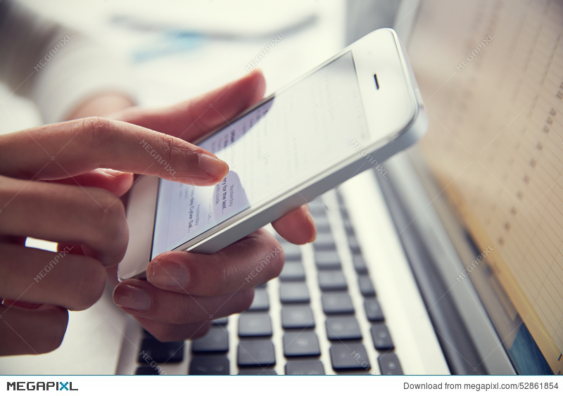 Stock Photos- Close Up Of Person At Laptop Using Mobile Phone ID 52861854 © Monkeybusinessimages   Megapixl